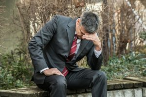 Mental health counselling for depression - businessman with head in hands