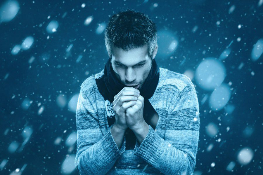 frigophobia fear of cold - man freezing blowing on hands