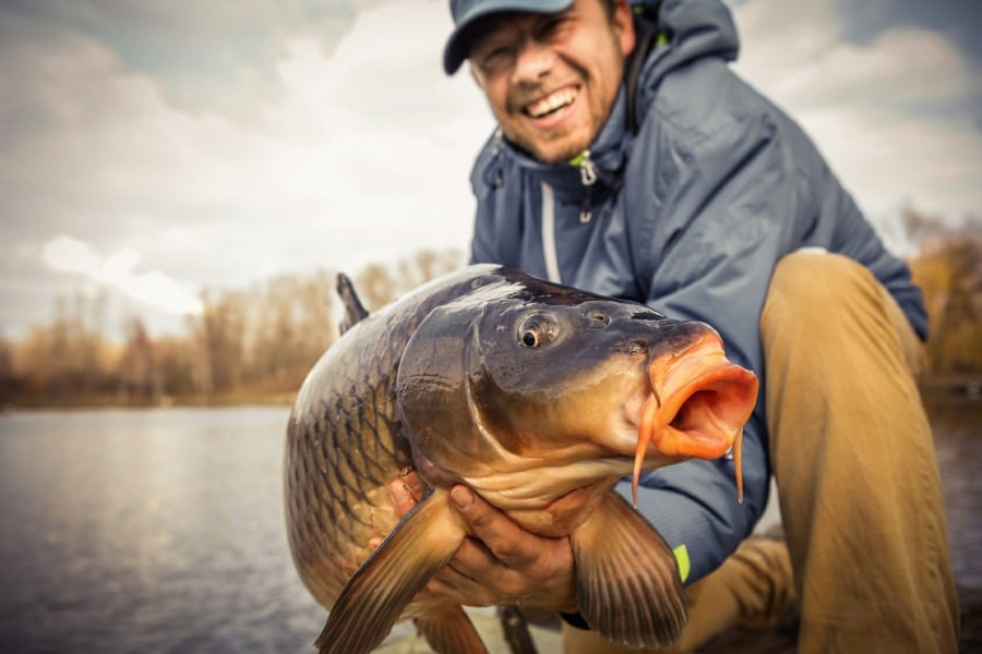 fear of fish ichthyophobia - fisherman with large fish in hands
