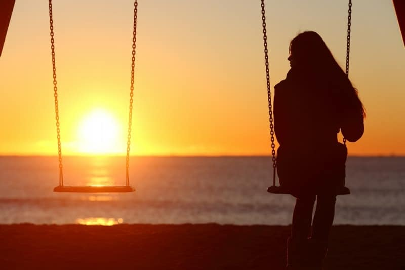 autophobia is the fear of being alone - lonely woman next to empty swing