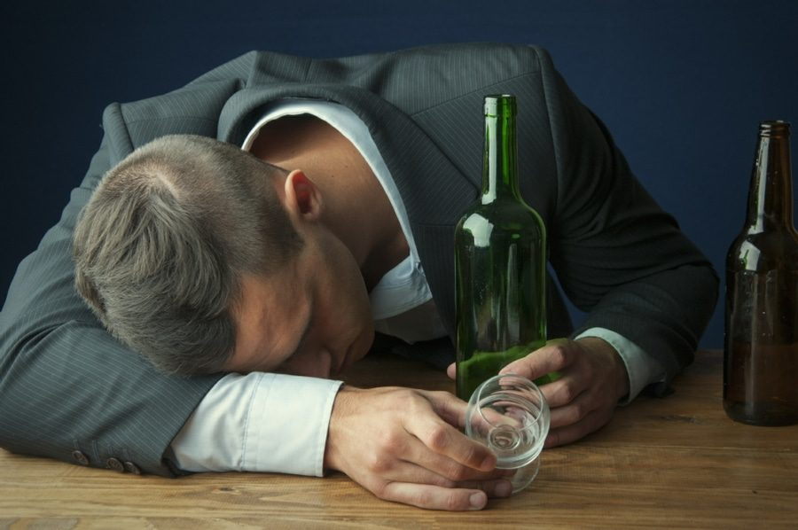 Alcohol abuse counselling - drunk man asleep next to empty bottle