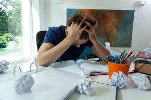 young man with anxiety sitting umongst scrunched-up paperwork