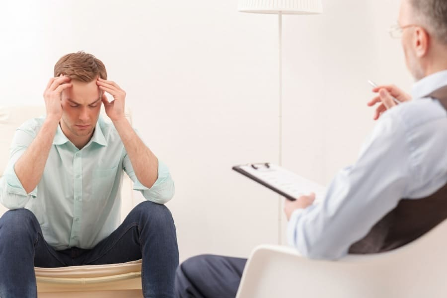 counselling session - therapist talking to young man with head in hands
