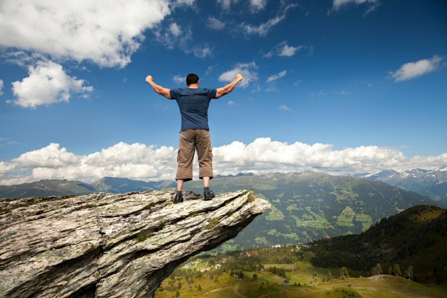 processing positive experiences - man standing on top of a mountain outcrop