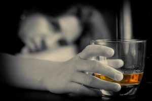 Mental health counselling for alcohol abuse - woman holding glass of whiskey