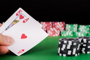 Mental health counselling for gambling addiction - mans hand holding playing cards in casino