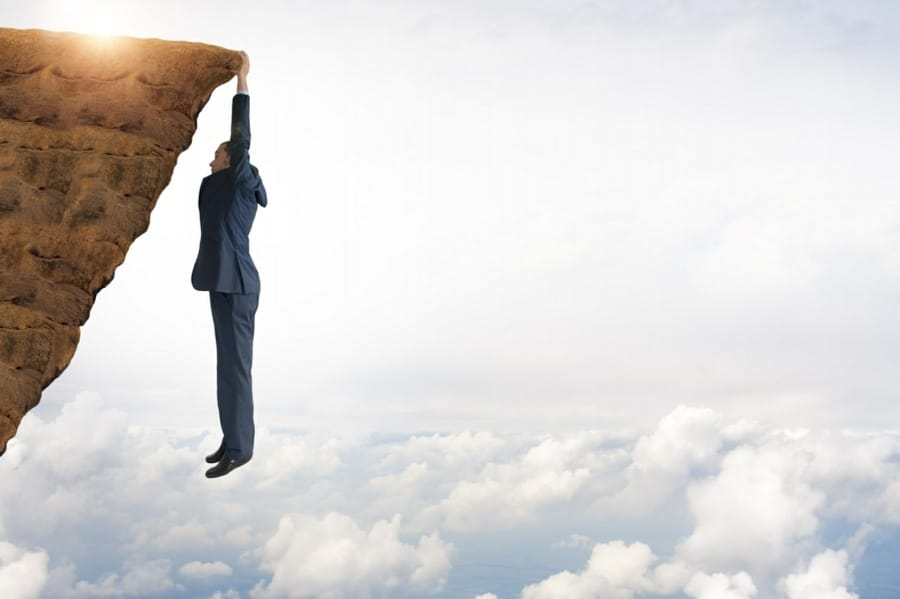 causes of work related stress - manager not coping hanging off a cliff metaphor