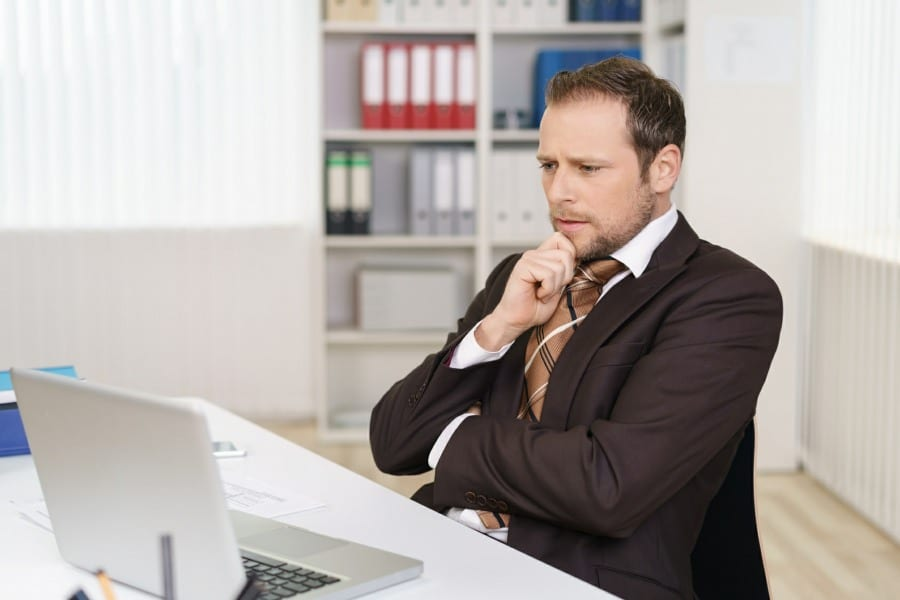 anticipatory anxiety on the face of a businessman at a computer