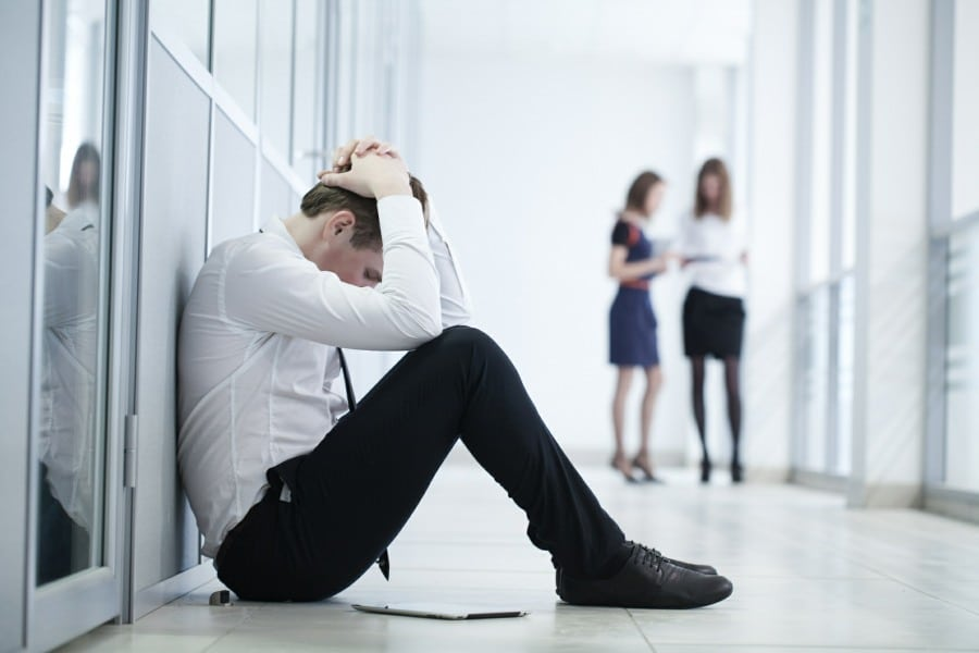 Young office worker with anxiety sitting in corridor with head in hands